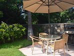 Barbecue Area with Picnic Table, Chairs and Umbrella.