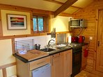 Kitchen with 4-burner hob, oven, microwave, fridge, kettle & toaster