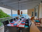 Covered outdoor dining overlooking the Atlantic with seating for 10. With 2 teak lounge chairs.