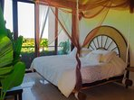 Guest bedroom overlooking the jungle with hanging king bed from natural beams.