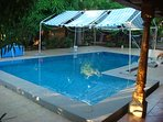 Relax by the pool under the palm and mango trees.  Lounge & use WiFi or just float in the pool.