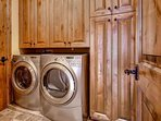 One of two laundry rooms (main & lower) with front-loading HE Whirlpool washer & dryer and custom large cabinets (with...