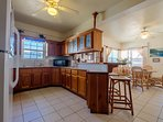 Fully equipped kitchen with counter and stools! The dining area is visible in the background.