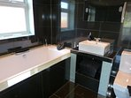 En suite with large bath, WC, basin and TV