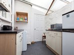 Utility room off the kitchen with fridge/freezer, microwave & washing machine.