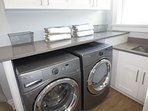Large laundry room equipped with Whirlpool Duet Washer & Dryer and large utility Sink