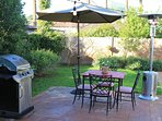 Outdoor patio with grill and seating for four