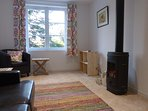 The sunny sitting room has views of the garden and a wood burner for the cooler seasons.