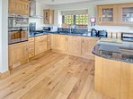 Kitchen area with oak units and granite work tops.