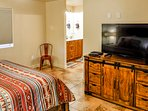 Master bedroom with 49-inch Smart TV and adjoining bathrrom