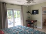 Spacious Master bedroom with desk and wall mounted Flat Screen TV and en suite bathroom.