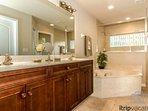 En suite master bath offers custom raised panel cabinetry, adult height vanity w/dual sinks, soaking tub, walk in...