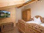 Schlafzimmer mit 2 Einzelbetten und Fernseher.