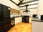 Kitchen with large fridge freezer, microwave and washing machine, fully fitted