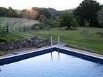 Pool with partial view of country road and landscape surrounding the house. Fully private.