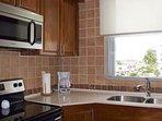 Modern kitchen, quartz countertop, stainless steel appliances.