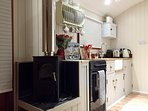 Hut kitchen with Nespresso coffee machine, kettle, undercounter fridge, Oven with hob, toaster, sink