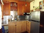 Well stocked kitchen, mid-size fridge with separate freezer and motion-activated faucet