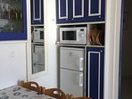 The kitchen with conventional microwave oven and the fridge freezer