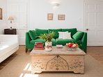 Velvet green three seater sofa ,close to the bookcase.