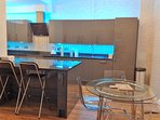 The kitchen and dining area, showing the kitchen area with blue neon lights.