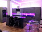 The kitchen and dining area, showing the kitchen area with purple neon lights.