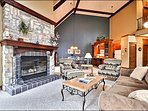 The Living Area Features a Beautiful Stone Fireplace, Large Picturesque Windows, and Cozy Furnishings