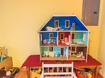 Lots of toys for children, including doll house and wooden trains with train tracks