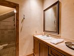 The en suite features a shower and single sink vanity.