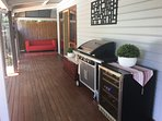 Private rear deck area provides dining furniture, BBQ and fridge