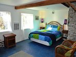 Lower level bedroom with a Queen bed, wicker chair, small ocean view and a private bathroom