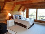 Upper level loft style bedroom with wall separation. Left side has a Queen bed, Cable flat screen TV/DVD, wood stove...