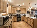 Renovated kitchen w granite countertops, breakfast bar and balcony.