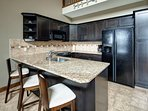 The modern and fully-equipped kitchen features a granite countertop