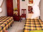 chambre à 2 lits, clim et moustiquaires, fenêtre sur jardin fleuri, armoire.