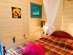 chambre grand lit porte sur jardin, climatisation, moustiquaires, fenêtre ventilante.