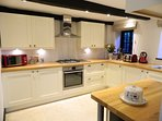 Modern kitchen with hob, oven, fridge, freezer, microwave, dishwasher and washer/dryer