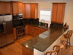 The kitchen has granite counters and stainless appliances