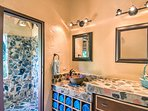 The vanity area of bathroom 2, leading to the outdoor stone shower.
