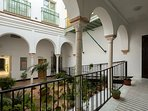 The apartment forms part of a Casa Palacio decorated with a colonnade of arches.