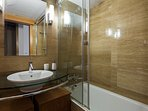 En-suite bathroom. The bathtub has an overhead shower.