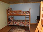 Lower level bunk bedroom with two sets of bunk beds and a play station