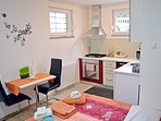 Fully equipped kitchen and dining table with 2 chairs. Garden view through the windows.