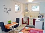 Fully equipped kitchen, dining table with 2 chairs and double bed. Garden view through the windows.