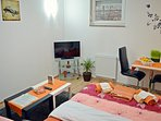 Studio apartment's living room with LCD TV, dining area and double bed (140x200 cm).