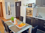 Fully equipped kitchen with dining area and entrance to the apartment.