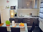 Fully equipped and modern kitchen with dining table and 5 chairs.