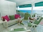 le salon sur la terrasse, détail: canapé, fauteuils, coussins. VUE mer exceptionnelle.