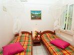chambre à 2 lits, clim et moustiquaires, fenêtre sur jardin, placard.