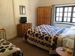 large bedroom with double and single bed overlooking garden and stream